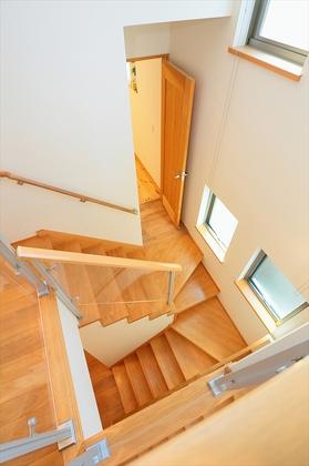 アクリルパネルで視界と安全性を確保した階段。中2階には約5帖の納戸スペースを確保。