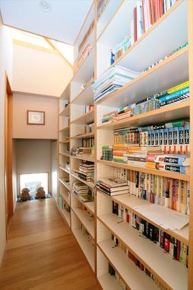 階段下には読書好きなお父様の書架を置き、わが家のライブラリー空間に。