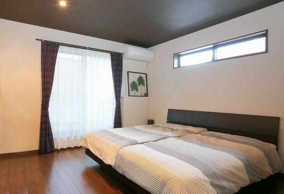 天井、床を濃いブラウンで引きしめた、落ち着きのある寝室。足元を照らすダウンライトや、横長の窓で光の量を調整しています。
