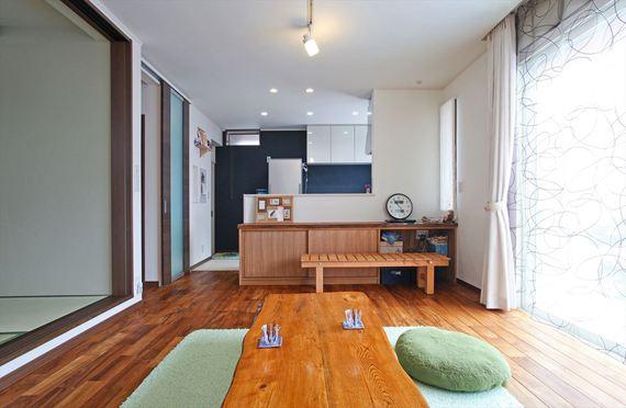 LDKは空間の用途を決めずに、住み手の要望に合わせて変化する柔軟性を持たせました。 フローングの力強い木目との相性を考えて選んだダークブラウンの建具や、 キッチンの紺色の和紙調クロスが空間をバランスよく演出します。