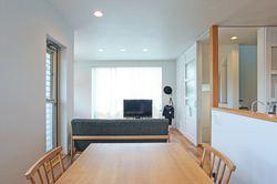 リビングの扉を開けると居室までフラットで繋がるので、坪数以上に広々と感じられます ソファーの正面の窓はテラスに繋がり、ブラインド越しに光と木々の緑を感じられます。