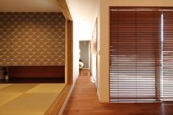 リビングを抜けて寝室へ。吊収納のアクセントクロスやウッドブラインド、細部にまでこだわったインテリアが目を楽しませる。
