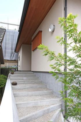 玄関へのアプローチは緩やかな階段で小さな子供も安心して上れます。 植栽の緑が風情を与えます。