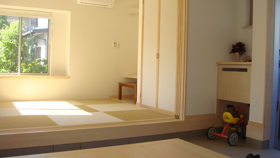 玄関から陽光差し込む客間を眺める