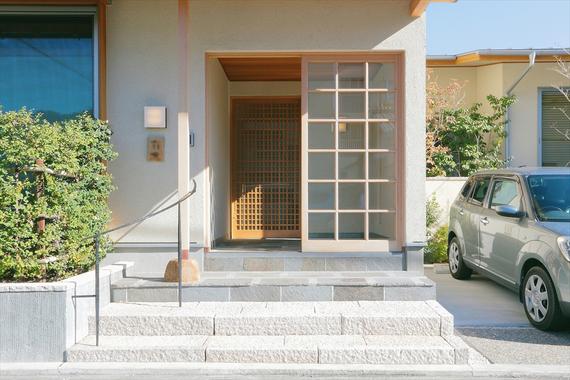 通りに面した玄関は二重の引き戸で視覚的・心理的に距離をもたせました。