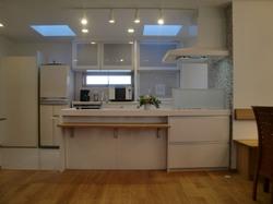 レンジフード横のモザイクタイルがかわいらしさを演出したオープンキッチン