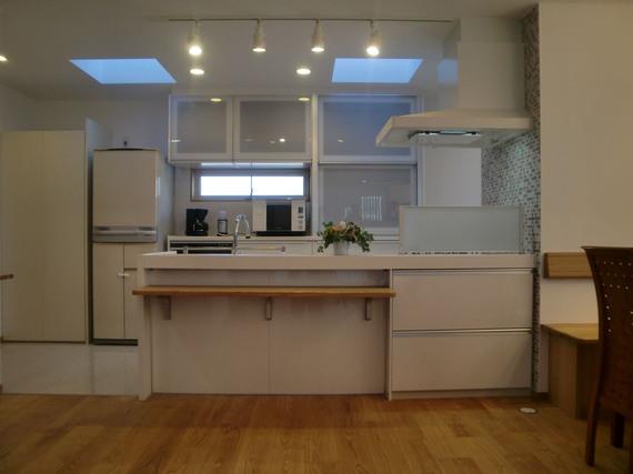 レンジフード側のモザイクタイルがかわいらしさを演出したオープンキッチン