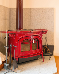 ご主人一目惚れのバーモントキャスティングの薪ストーブ。コトコト煮込みやオーブン料理などのストーブクッキングも楽しめる。オブジェとしても可愛い松ぼっくりは天然の着火剤に。