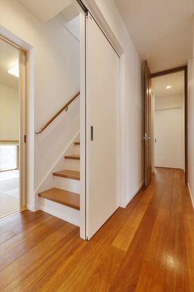 両側とも引き戸によって隠してしまうことの出来る階段です。 引き戸を閉めていると誰も階段があることに気付きません。 リビングを通っての階段ですが、引き戸を閉めれば空調も快適に保て実に妙案です。