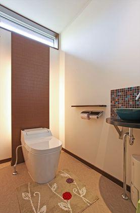 間接照明・アクセントタイルや陶器の手洗いボウルを採用した魅せるトイレ。