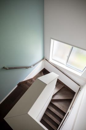 無機質になりがちな階段もブルーグレーのクロスでひと味違った印象に。